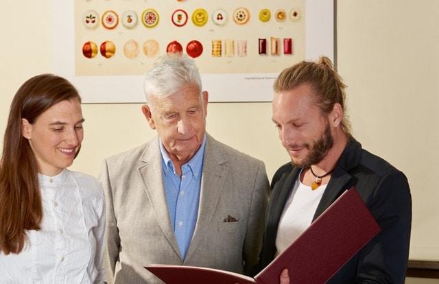 Friedrich W. Heller blättert gemeinsam mit den Zuckerlmachern der Zuckerlwerkstatt Christian Mayer und Maria Scholz im Katalog der Firma Heller