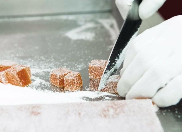 Fruchtgelees werden in der Zuckerlwerkstatt per Hand in kleine Würfel geschnitten