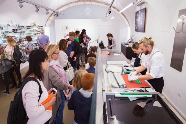 Kunden schauen dabei zu, wie die Bonbons live in der Schaumanufaktur der Zuckerlwerkstatt in Salzburg produziert werden